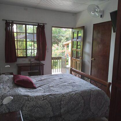 Recámara, vista de la cama queen, escritorio con router wifi privado, salida a la terraza