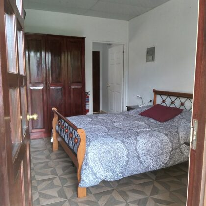 Recámara, vista de la cama y del closet, entrada a la cocina