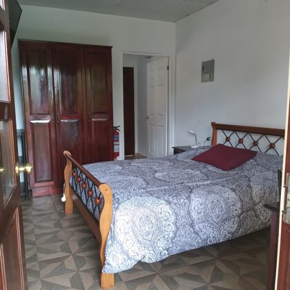 Bedroom: queen-size bed, wardrobe, fire extinguisher, door to the kitcheb